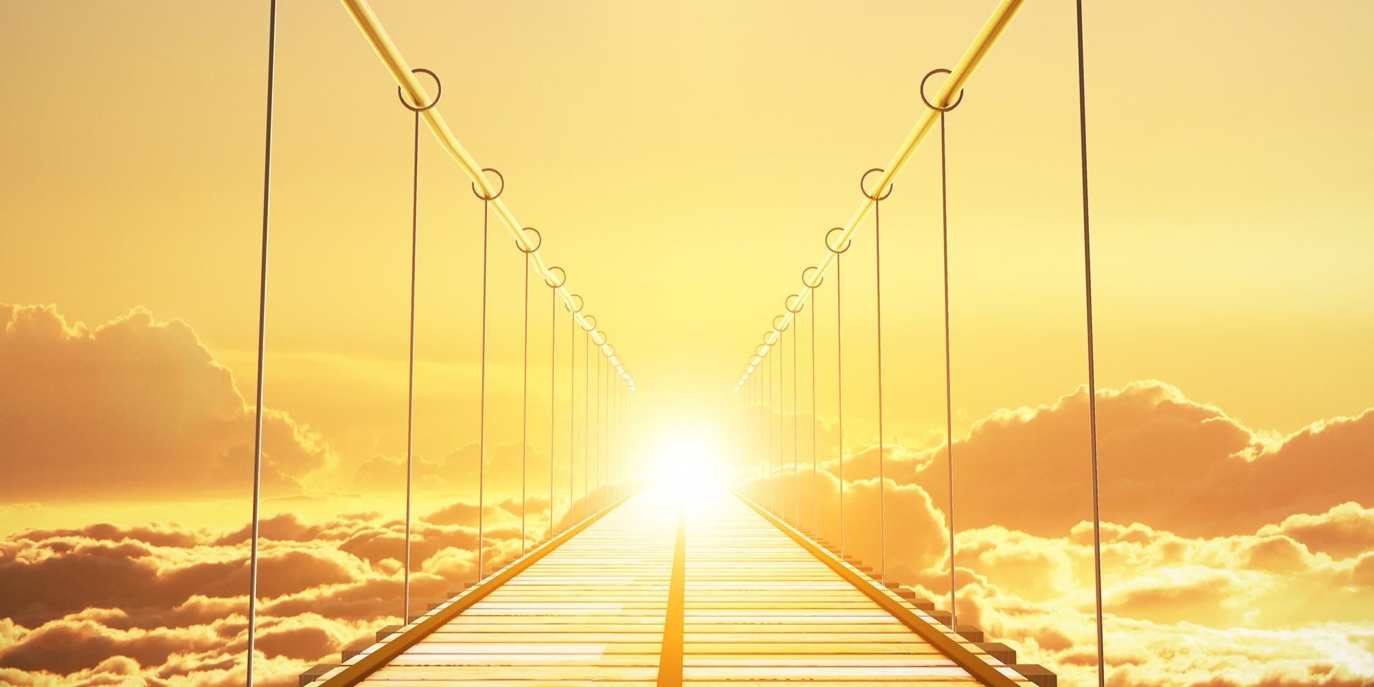 bild som visar en hängbro med en soluppgång i fjärran