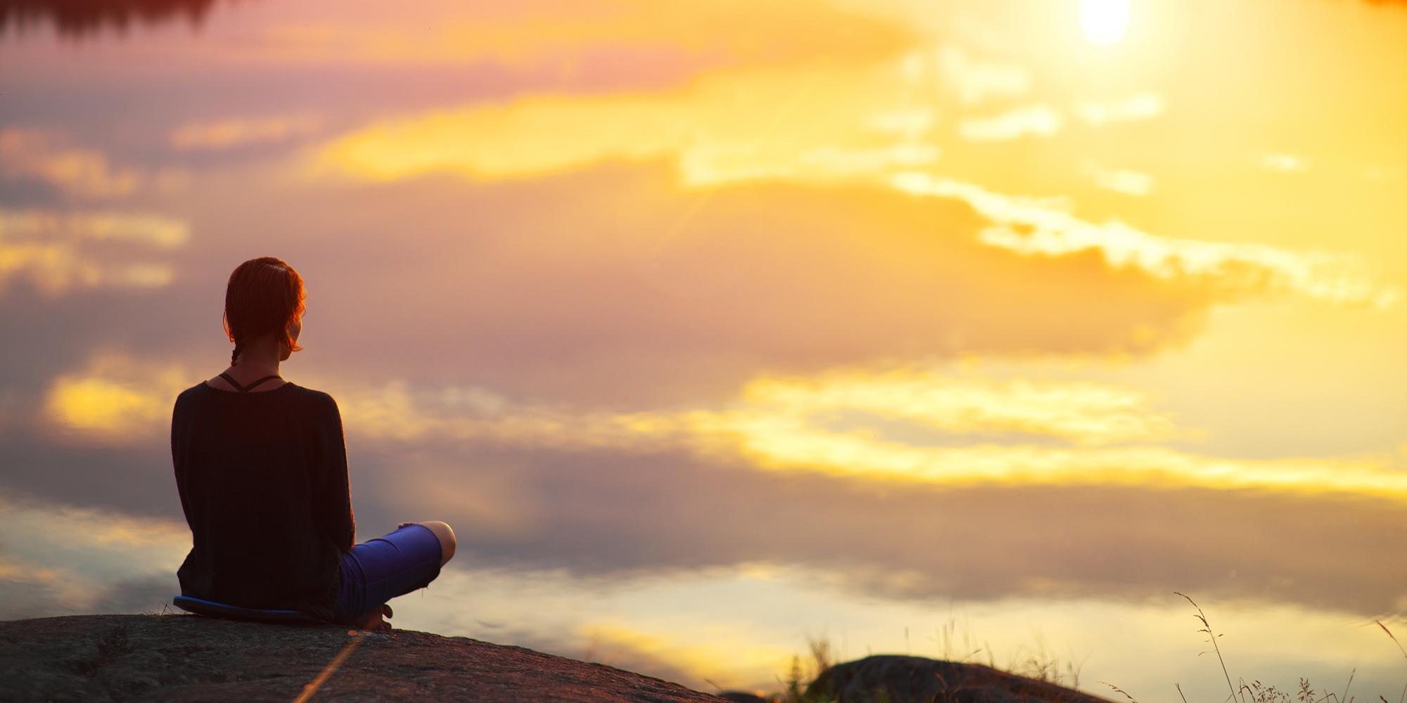 bild som visar en kvinna på en klippa som tittar ut över havet