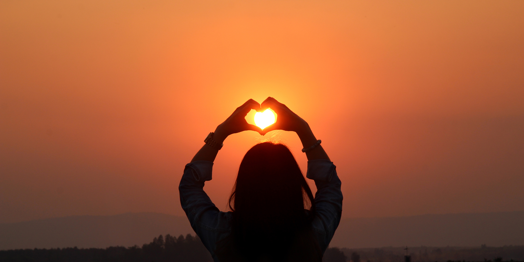 bild som visar en soluppgång med händer som bildar ett hjärta