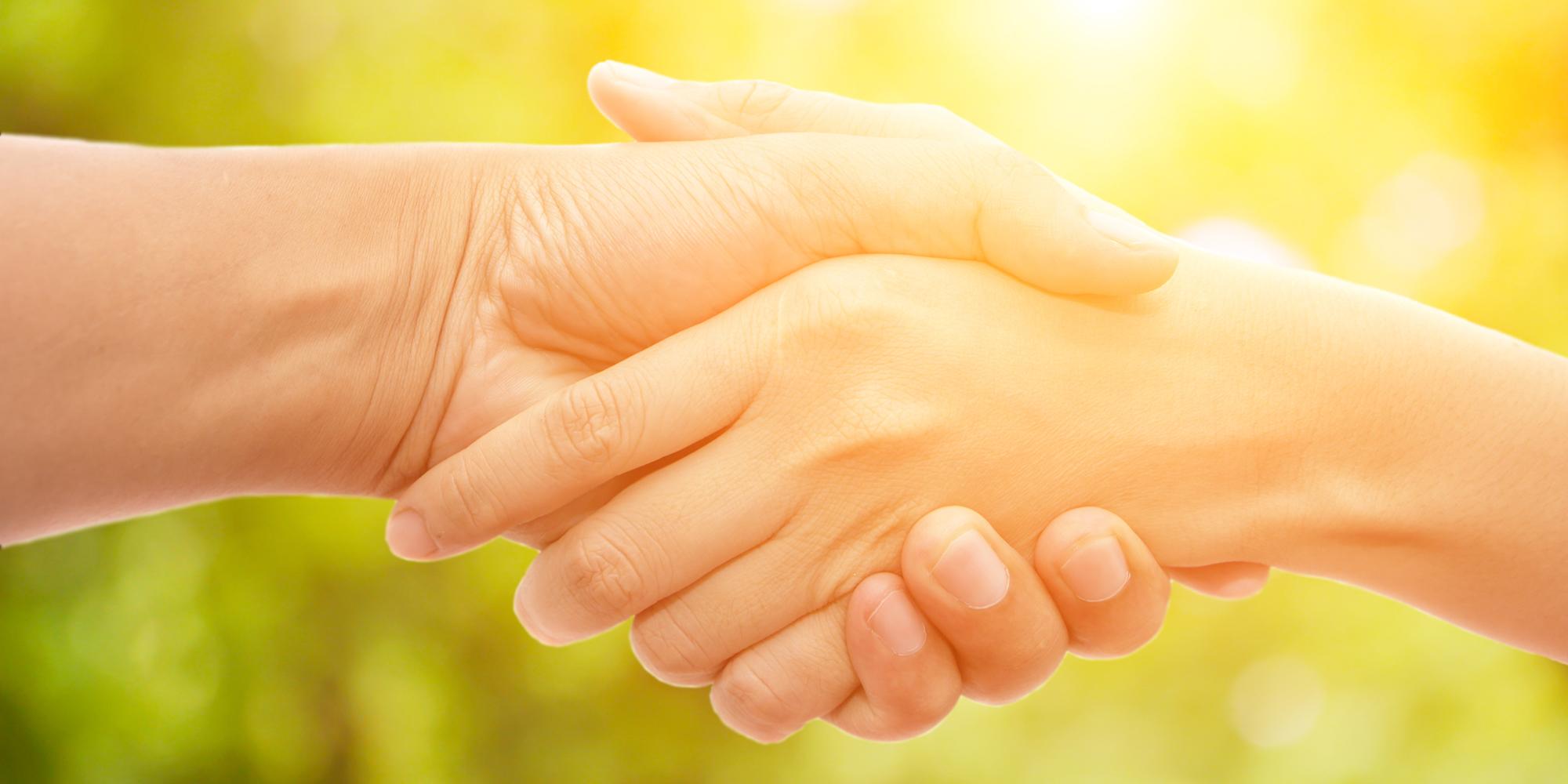 bild som symboliserar hopp med kvinnohänder som möts