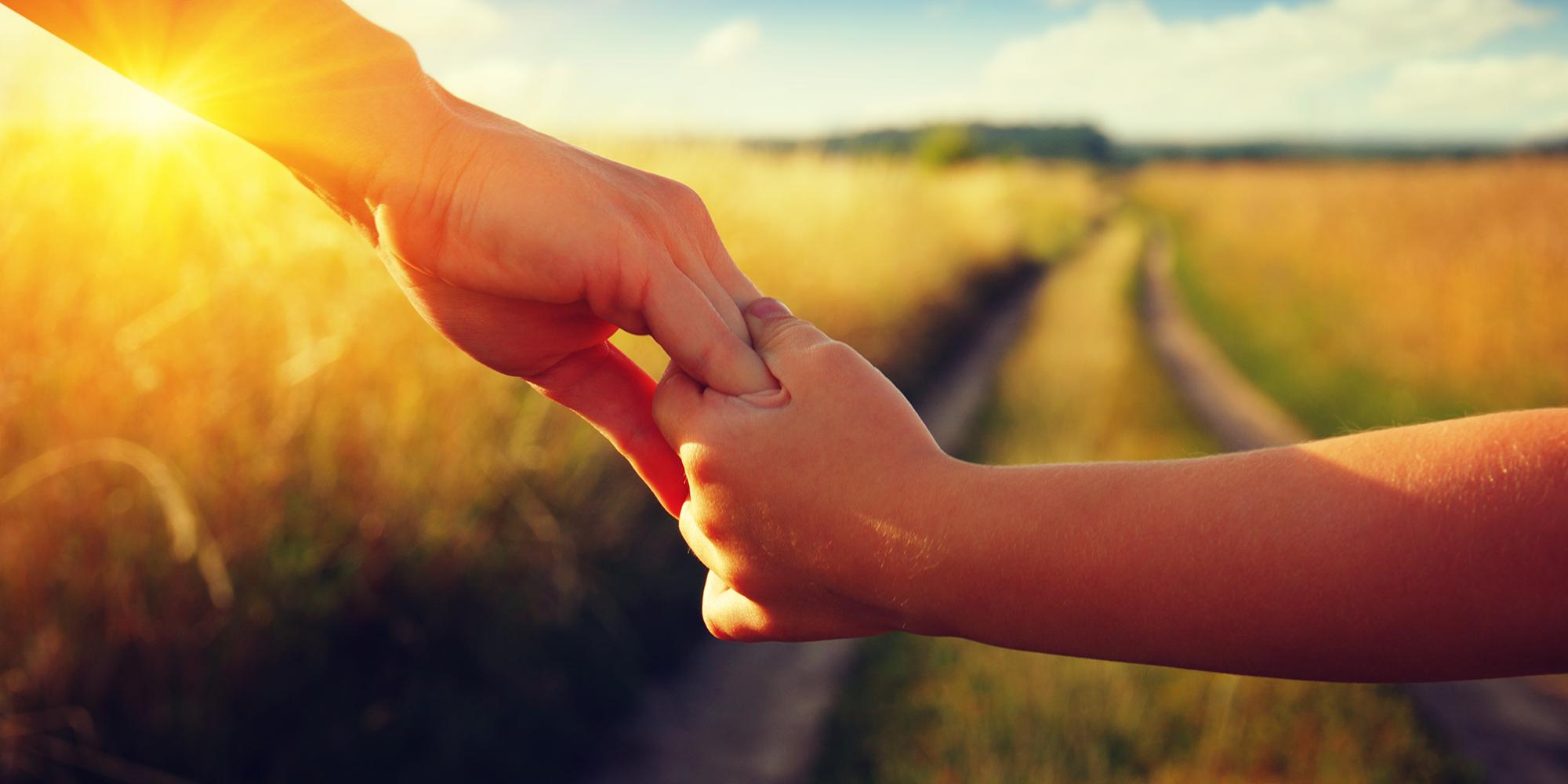 bild som visar 2 händer som hålls när de går längs en väg